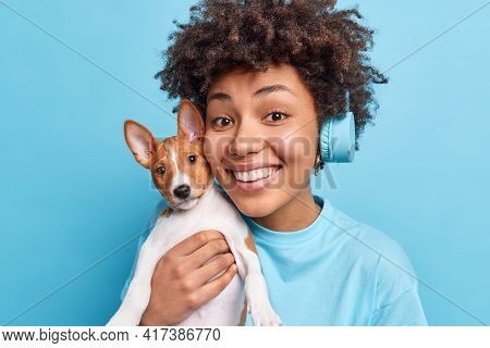 Photo Of Joyful Beautiful Afro American Girl Has Curly Hair Smiles Broadly Poses With Pedigree Dog E