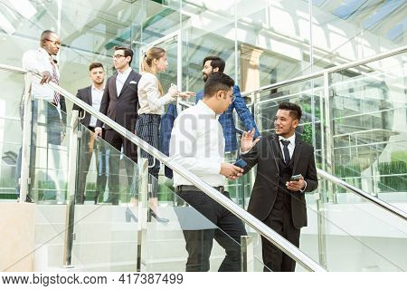 Young Business People Arego Down The Stairs And Talking On The Background Of Glass Offices. Corporat