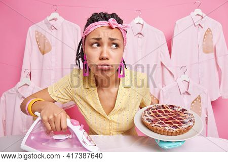 Housekeeping And Domestic Chores Concept. Sad Distressed Dark Skinned Woman With Dreadlocks Holds Ba