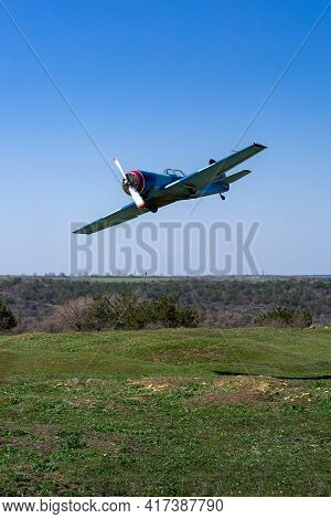 Small Single Propeller Plane Flies Low Over The Ground Hilly Landscape With Green Grass And Blue Sky