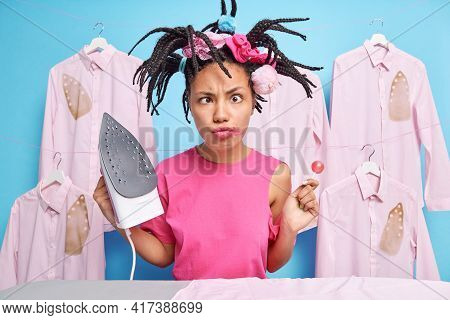 Comic Female Teenager Crosses Eyes Makes Funny Grimace Foolishes Around While Doing Ironing At Home