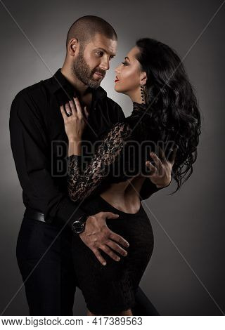 Couple In Love. Romantic Fashion Woman In Black Dress And Man Dancing. Models Portrait Embracing And