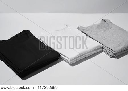 Three Folded Monochrome T Shirts Gray, Black And White Isolated Over Gray Background. Clothes, Fashi