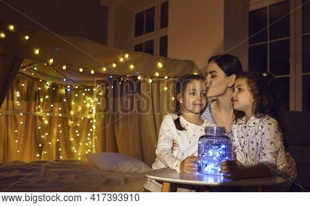Caucasian Mother Kiss Children On Forehead Before Bedtime At Cozy Home Bedroom