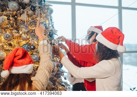A Young People Decorates The Christmas Tree In Medical Masks.