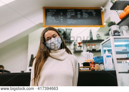 Girl Wearing Protective Mask Sitting In Coffee Shop