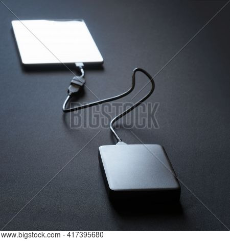 Black External Hard Drive Connected With A Wire To A Smartphone, Tablet Or Phablet. Black Background