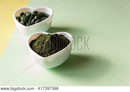 Organic Spirulina Powder And Pills In A Heart Shaped Plate