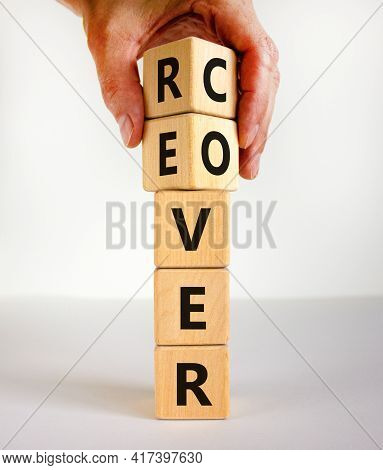 Recover Symbol. Concept Word 'recover' On Wooden Cubes On A Beautiful White Table. Businessman Hand.