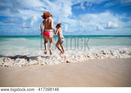 Girls Jump In Shore Waves On A Sunny Day, Dominican Republic
