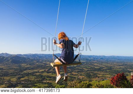 Red Haired Teenage Girl Swinging On A Swing At Montana Redonda. Dominican Republic