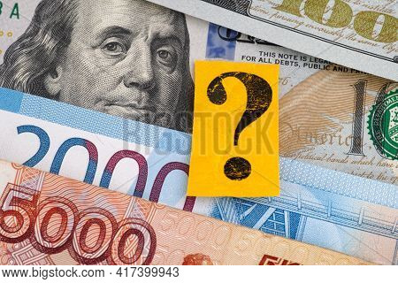 Russian Rubles And One Hundred Dollar Bills And A Yellow Paper Note With A Question Mark On It. Clos