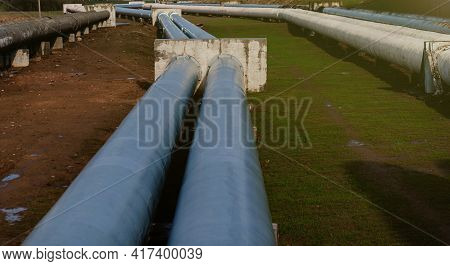 Elevated Heat Pipes. Pipeline Above Ground, Conducting Heat To Heat City. Urban Line In Metal Insula