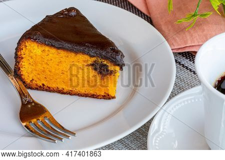 Carrot Cake With Chocolate Icing, Accompanied By A Cup Of Coffee