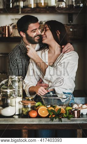 Young Happy Couple Hugging Making Dough For Baking Pie Together