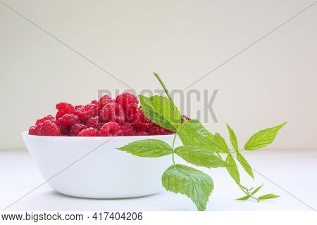 Big Pile Of Fresh Raspberries And Leaf In Transparent Bowl On The White Background