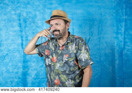 Person Dressed As A Tourist With A Printed Shirt And With His Hand On His Face As If He Were On The