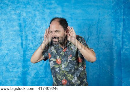 Person Dressed As A Tourist With A Patterned Shirt And With His Hand Over His Ear Making A Gesture O