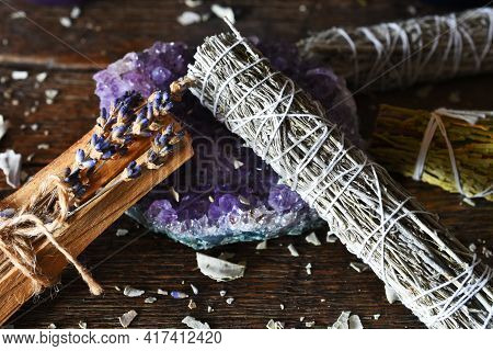 A Close Up Image Of White Sage Smudge Bundle And Amethyst Crystal.