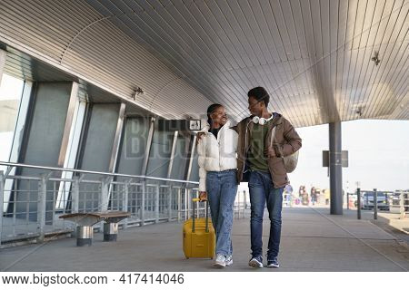Happy Black Couple Of Tourists With Suitcase Leave Airport After Arrival Hugging Talking. Happy Trav