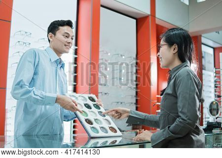 A Male Shop Clerk Holds A Sample Of Eyeglass Lenses And A Customer Points His Finger To Select