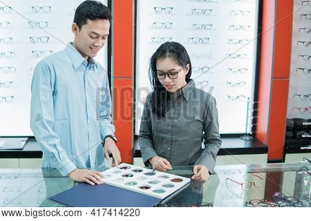 A Male Shop Clerk Holds A Sample Of Eyeglass Lenses And A Customer Points His Finger To Select Eyegl