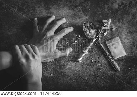 Human Hand Of A Drug Addict And A Syringe With Narcotic Syringe Lying On The Floor, World Anti Drug