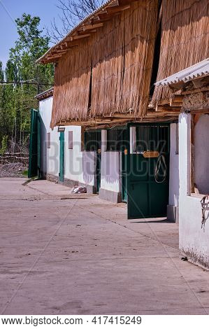 Stables In The Village. View Of The Stable, Attic With Hay For Horses
