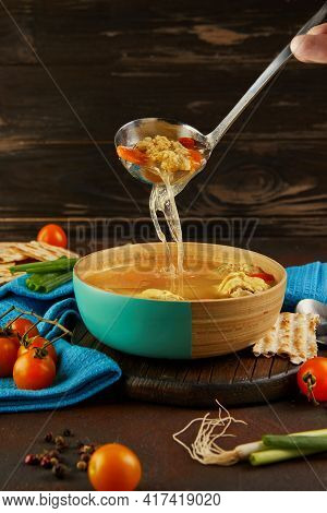 Soup With Matzo Dumplings And Chicken With Carrots And Tomatoes Is Poured Into Bowl With Ladle. Heal