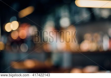 Coffee Shop Blur Background With Bokeh Lights. Blurred Outlines Of Bar And Tables, Dim Lights