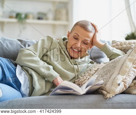 Funny Moment. Cheerful Middle Aged Woman Laughing While Reading Interesting Book And Relaxing On Sof