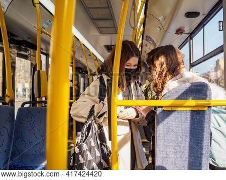 Moscow. Russia. April 12, 2021. Two Cheerful Girls In Protective Masks In A City Bus. Necessary Meas