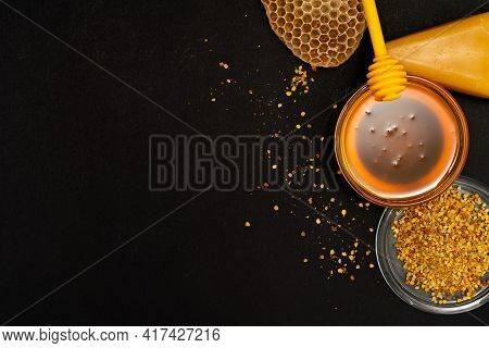 A Ladle Of Honey On The Background Of A Honeycomb Of A Bee. Honey Tidbit In A Glass Jar Honey Spoon,