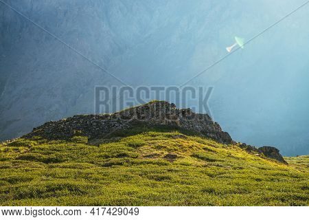 Colorful Green Landscape With Rocks And Hills On Background Of Giant Mountain Wall In Sunlight. Mini