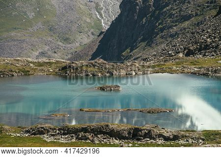 Stone With Mosses In Turquoise Clear Water Of Mountain Lake In Sunlight. Sunny Scenic Nature Landsca