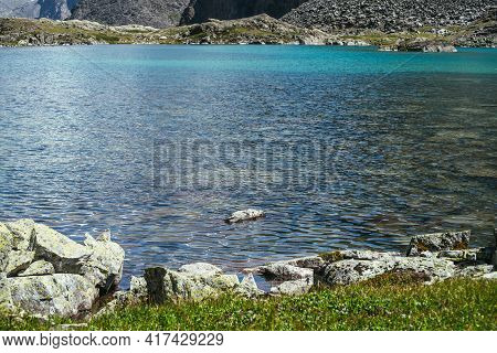 Sunny Beautiful Landscape With Meditative Ripple On Azure Calm Water Of Mountain Lake In Sunlight. R