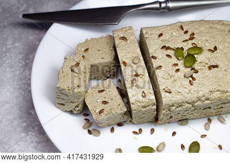 Halva Close Up On A White Plate On A Gray Background. Traditional Oriental Dessert Candy Halva. Halv