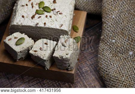 Halva Close-up On A Blackboard On A Brown Wooden Background. Traditional Oriental Dessert Sweet Halv
