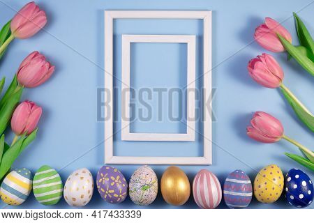 Tulips Flowers And Easter Eggs With Wooden Frame On Blue Background. Card For Happy Easter. Waiting