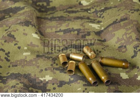 A Few Random Casings On Camouflage Cloth. A Group Of Pistol And Rifle Empty Casings Lie On Military