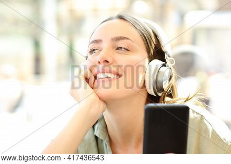 Happy Woman Wearing Headphones And Holding A Smart Phone Listening To Music Dreaming In A Coffee Sho