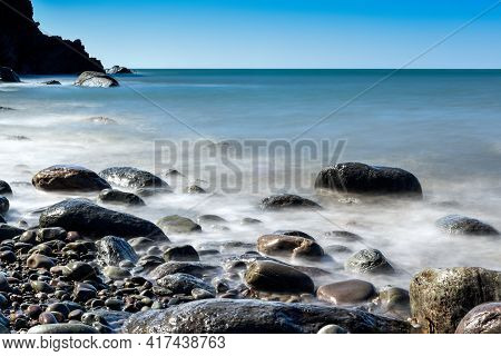 Peaceful Rocky Beach With Long Exposure Of Calm Blue Water