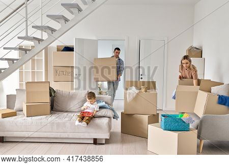 Young Family Couple Homeowners With Cute Kid Child Son Packing Or Unpacking Boxes On Moving Day. Fam