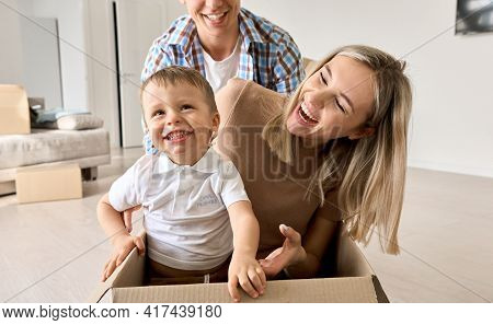 Cute Excited Kid Son Riding In Box On Moving Day With Parents. Happy Family Young Couple New Home Ow