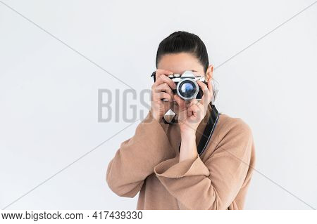 Front View Of Stylish Pretty Girl Taking A Picture With Vintage Camera.isolated On White Background.