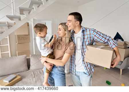 Happy Family Couple New Home Owners Holding Toddler Kid Child Son And Cardboard Box On Moving Day St