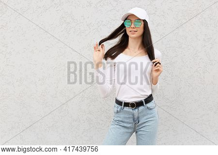 Attractive Young Female With Dark Hair Wearing Jeans, Shirt, Baseball Cap And Sunglasses, Touching H