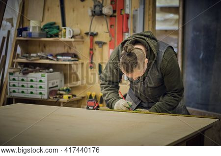 Carpenter Holding A Measure Tape On The Work Bench. Woodwork And Furniture Making Concept. Carpenter