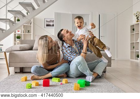 Happy Young Couple Having Fun With Cute Kid Boy In Modern Living Room. Parents Playing With Funny To