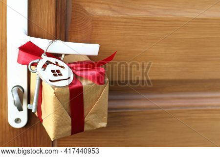 Gift With House And Key Symbols Hanging On A Doorknob. Holiday Surprise For The New Year